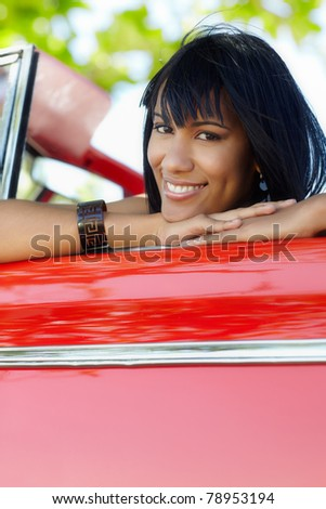 young adult brunette woman leaning on convertible red car and looking at camera. Vertical shape, front view, copy space