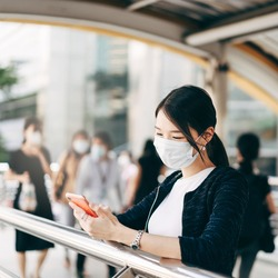 Young adult business asian working woman wear face mask for protect virus corona or covid19 and air pollution. Using mobile phone application. Urban people lifestyle with public health on day concept.