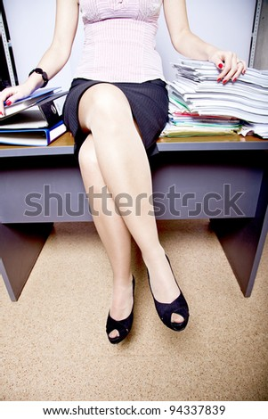 young adult business woman sitting on a table among the piles of papers and documents