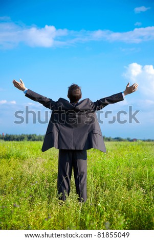 young adult businessman in a field with outstretched arms to the sky looks into the distance