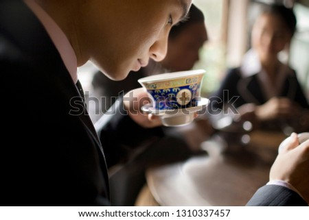 Young adult businessman smelling a cup of tea.