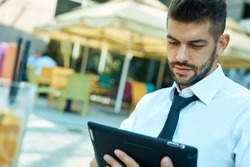 Young adult businessman using tablet outdoor in cafe.