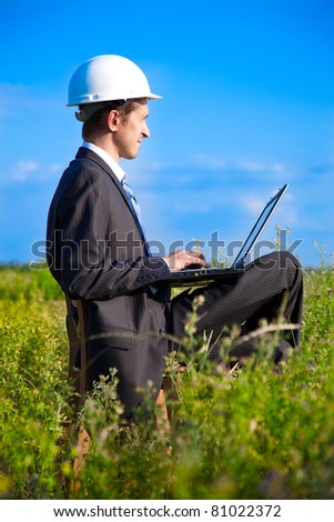 young adult businessman wearing a helmet sitting in a box on a chair with a laptop. focus on businessman
