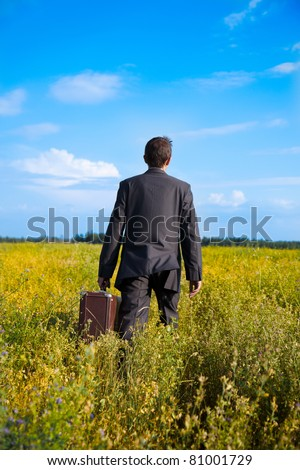 young adult businessman with old two suitcases businessman in the field