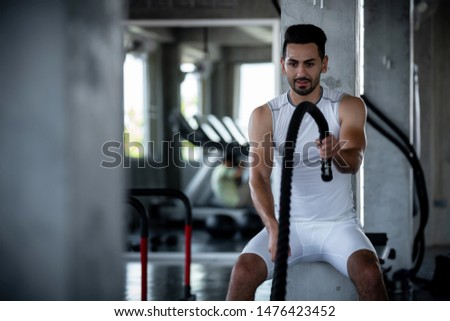 Young adult caucasian athlete sport bodybuilding man in sportswear doing cardio battle rope exercise workout fitness pumping up muscles during training class in gym sport club for strong healthy.