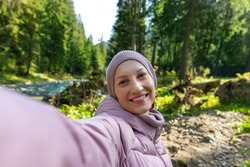 Young adult caucasian beautiful happy smiling woman in warm jacket and hat making selfie shot by cell phone during walk in scenic green woods pine forest river. Person enjoy walking nature outdoors