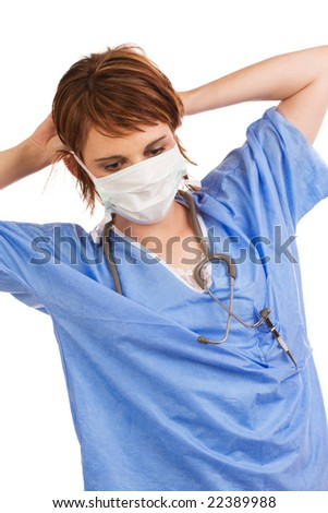 Young adult Caucasian female medical assistant dressed in scrubs putting on a protective mask