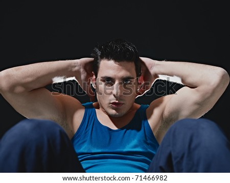 young adult caucasian male in blue sportswear exercising abdominals on black background, looking at camera. Horizontal shape, front view, copy space
