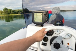 Young adult caucasian man POV enjoy having fun driving fast motorboat with family on pond water surface at sunset evening time. Male person sailing on speedboat with sonar and compass equipment tools