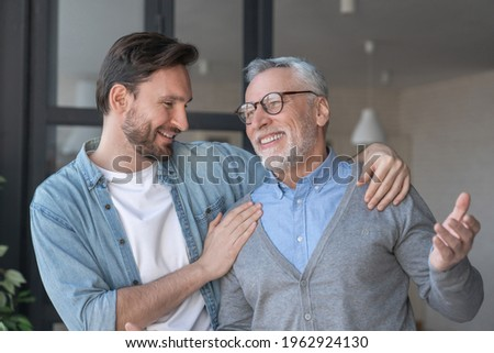 Young adult caucasian son listening and supporting his old elderly senior father at home indoors.Happy father`s day! Care and love concept. I love you, dad!
