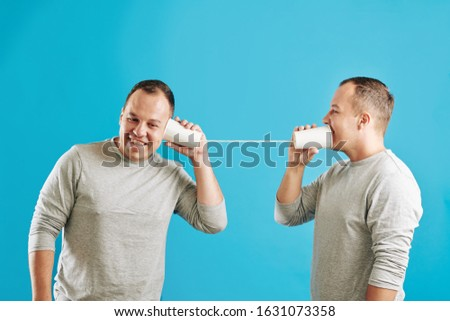 Young adult Caucasian twin brothers playing with plastic cup telephone, blue wall background