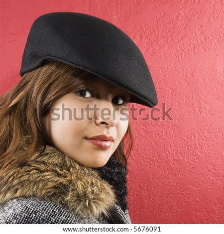 Young adult Caucasian woman wearing flat hat looking at viewer.