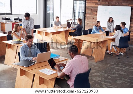 Young adult colleagues working in busy office, elevated view