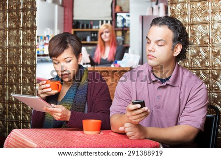 Young adult couple at cafe sneaking a peek at their devices