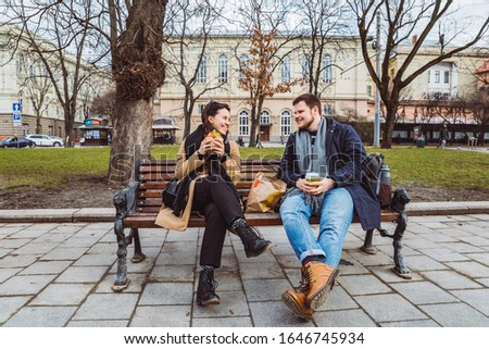 young adult couple eating fast food on bench of city park