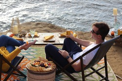 Young adult couple enjoy a seaside luxury picnic with beach chairs, food, drinks, and gourmet charcuterie cheese board with an ocean view on the cliffside