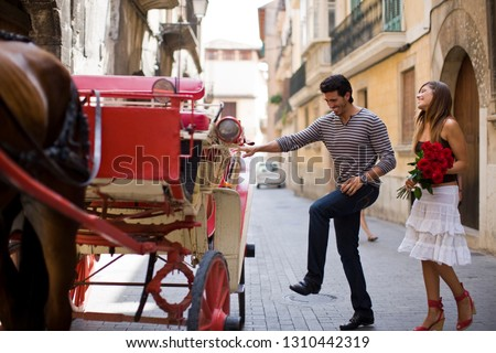 Young adult couple getting into a horse-drawn cart.