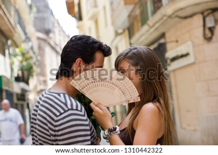 Young adult couple hiding their face behind a fan.