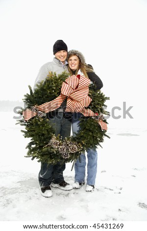 Young adult couple in the winter holding a Christmas wreath and with arms around one another. Vertical shot.