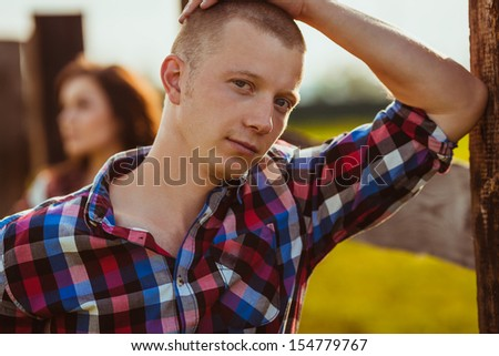 young adult couple on the farm standing near fence, man in the foreground #154779767