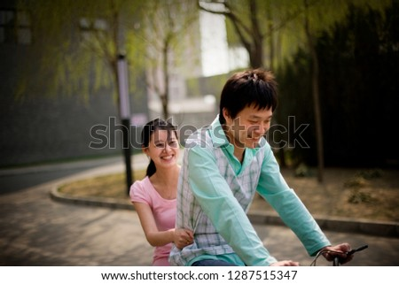 Young adult couple riding a bicycle along a park.