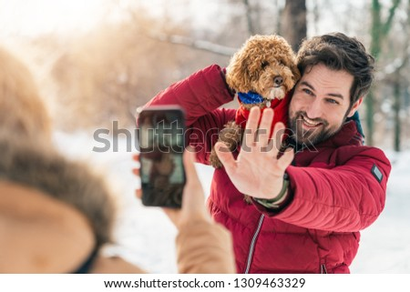 Young adult couple taking a picture and enjoying the day with dog poodle outdoors