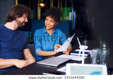 Young adult coworkers analyzing the documents