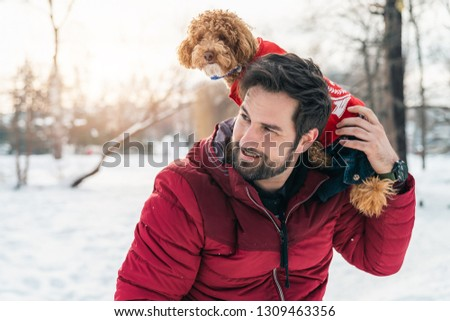 Young adult enjoying a day in the park with his dog poodle
