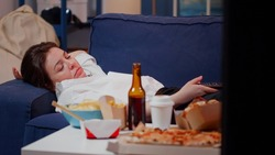 Young adult feeling sleepy while watching television on sofa in living room. Tired woman falling asleep with remote control after work and eating fast food meal, laying on couch at home