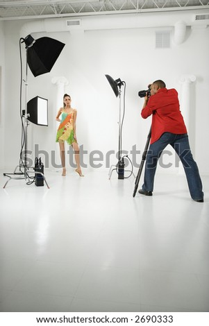 Young adult female Caucasian model being photographed in studio by young adult African American male photographer.