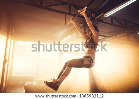 Young adult female doing chin-ups