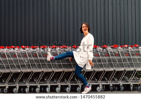 Young adult female kicking air near shopping trolleys.