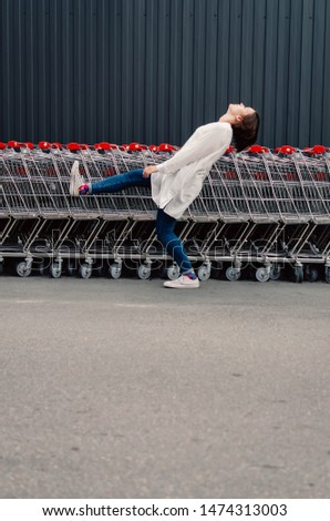 Young adult female kicking air near shopping trolleys. #1474313003