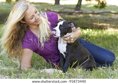 Young adult female laying on green grass with her Pit Bull puppy