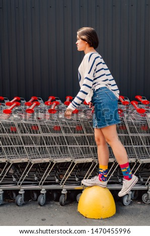 Young adult female staying near shopping trolleys. #1470455996
