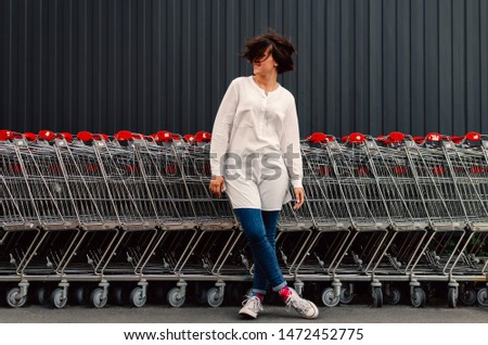 Young adult female staying near shopping trolleys. #1472452775