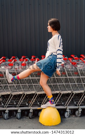 Young adult female staying near shopping trolleys. #1474313012