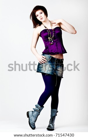 Young adult female wearing a purple corset looking down