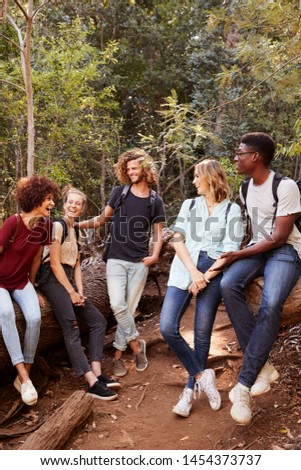 Young adult friends hiking in a forest resting on a fallen tree, full length, vertical
