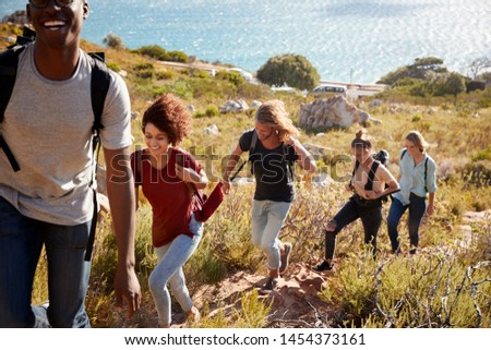 Young adult friends hiking single file uphill on a path by the coast, full length