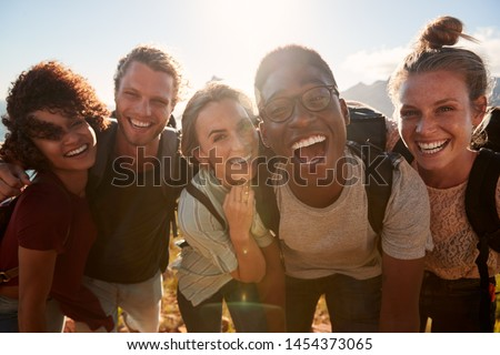 Young adult friends on a hike celebrate reaching the summit, smiling to camera, close up