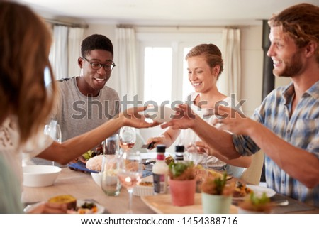 Young adult friends passing a dish across the dinner table at lunch, close up