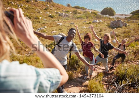 Young adult friends posing and taking photos of each other during a hike uphill on a coastal path