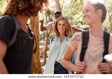 Young adult friends talking as they hike through a forest together, close up