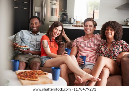 Young adult friends watching TV with food and drinks at home