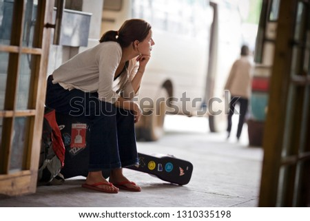 Young adult girl with a backpack and a guitar travelling.