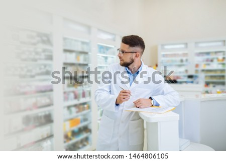 Young adult. Handsome brunette standing at the table while doing inventory #1464806105