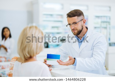 Young adult. Handsome male person wearing sterile uniform while working in drug store