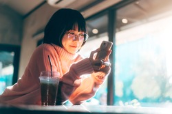 Young adult happy asian woman wear eyeglasses using mobile phone for social media application. Text online message at indoor cafe on day. Background with window and warm sunlight on winter season.