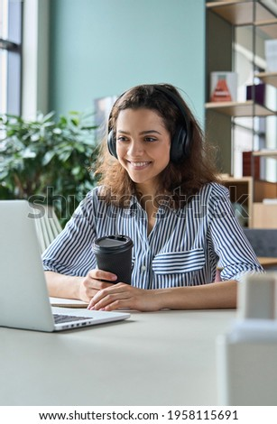 Young adult happy smiling Hispanic indian student wearing headphones talking online chat meeting holding coffee using laptop in virtual office. College female student learning remotely.